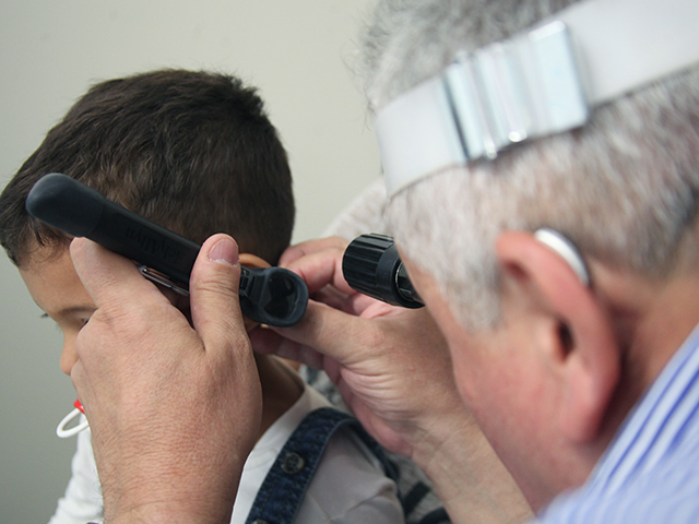 Fotografia mostra profissional examinando ouvido de paciente criança usando equipamentos de otorrinolaringologia.